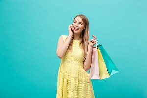 Portrait of happy fashion caucasian woman with shopping bags calling on mobile phone. Isolated on blue background.