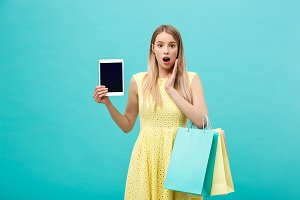 Excited shocked good-looking young woman in yellow dress while holding tablet and shopping bags.
