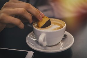 hand with biscuit in the cup of coff
