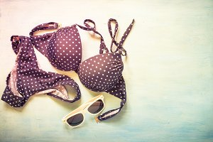 Swimsuit and sunglasses on light blue background.
