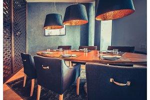 Orange table, blue chairs, lamps. Restaurant decor.