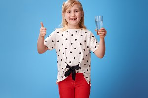 happy child with glass of water showing thumbs up on blue