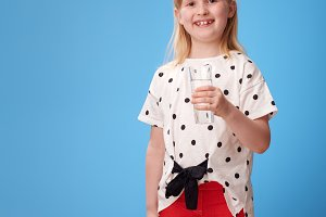 happy modern girl in red pants on blue with glass of water
