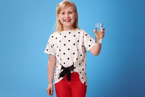 happy modern girl in red pants on blue showing glass of water