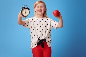 smiling modern child showing alarm clock and an apple on blue