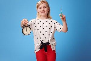 smiling modern girl showing alarm clock and syringe on blue