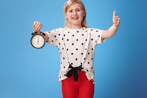 happy modern child with alarm clock showing thumbs up on blue