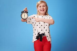 happy modern child in red pants on blue poiting at alarm clock