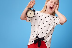 stressed modern child in red pants on blue with alarm clock