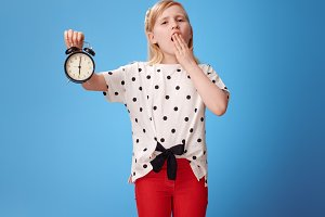 modern child showing alarm clock and yawing on blue