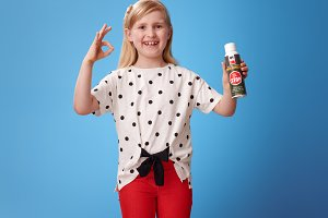 happy modern girl showing insecticide and ok gesture on blue