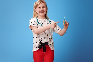 smiling child with stethoscope pointing at syringe on blue