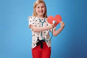smiling girl with stethoscope listening to paper heart on blue