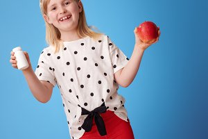 smiling girl with an apple and bottles of vitamins on blue