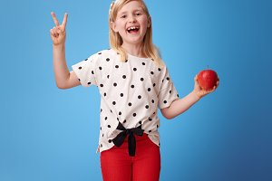 happy modern child with an apple showing victory on blue