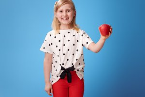 smiling modern girl in red pants on blue showing an apple