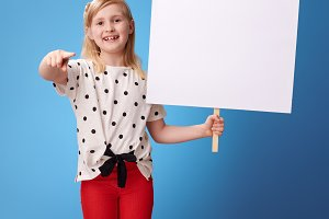 smiling child with blank poster pointing in camera on blue