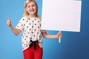 happy modern child showing blank poster and thumbs up on blue