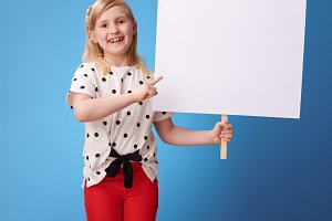 happy modern girl pointing at blank placard on blue