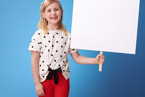 happy modern child in red pants on blue showing blank placard