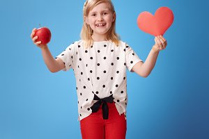 smiling modern child showing paper heart and an apple on blue