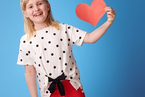 smiling modern child in red pants on blue showing paper heart