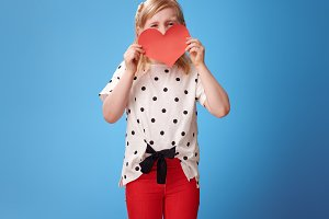modern child in red pants on blue hiding behind paper heart