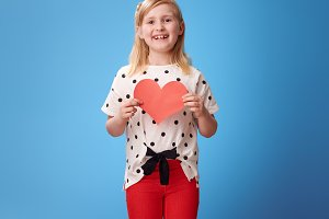 smiling modern girl in red pants on blue showing paper heart