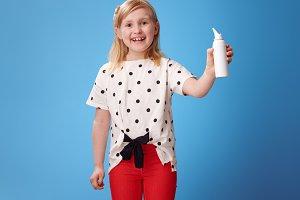 smiling modern girl isotonic seawater nasal spray on blue