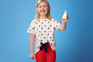 happy modern child in red pants on blue showing nasal drops