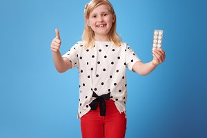 happy modern child showing thumbs up and and pill on blue