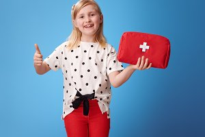 smiling child showing first-aid kit and thumbs up on blue