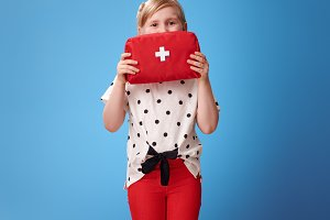 happy child holding first-aid kit in front of face on blue