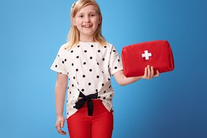 smiling modern girl in red pants on blue showing first-aid kit