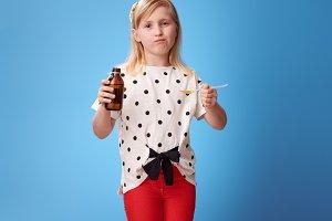 sad modern girl taking spoon of children's suspension on blue