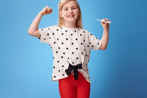 happy modern girl showing biceps and thermometer on blue