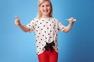 smiling modern girl showing thumbs up and thermometer on blue