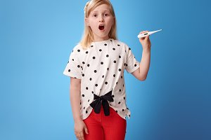 surprised modern girl in red pants on blue showing thermometer