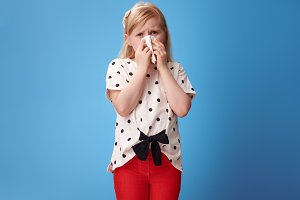 unhappy modern child in red pants on blue blowing nose