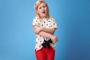 unhappy modern child in red pants on blue with pain in hand