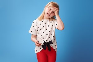 unhappy modern child in red pants on blue having headache