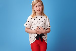sad modern child in red pants on blue with abdominal pain