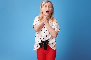 modern child in red pants on blue with neck pain
