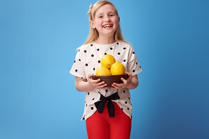 smiling modern girl showing plate with lemons on blue