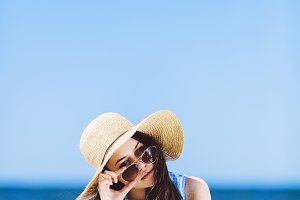 Young pretty woman laying on the beach, holding her sunglasses.