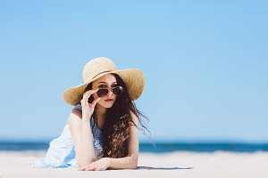 Pretty girl in straw hat laying on the sandy beach