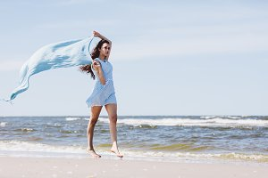 Pretty girl walking by the sea with a blue waving scarf.