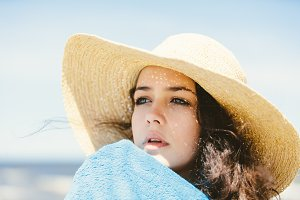 A portrait of a young girl in a straw hat.