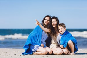 Family sitting on a beach, older sister pointing her finger