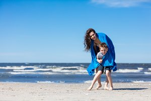 Older sister holding her little brother on the beach.